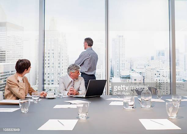 Businessman looking out conference room window at cityscape