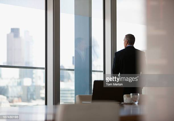 businessman looking out conference room window - authority stock pictures, royalty-free photos & images