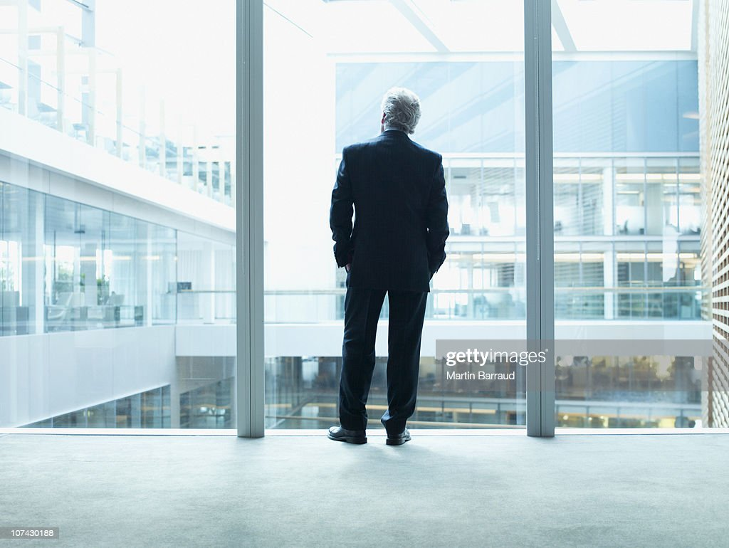Businessman looking out glass wall in office : Stock Photo