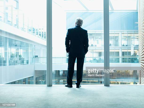 Businessman looking out glass wall in office