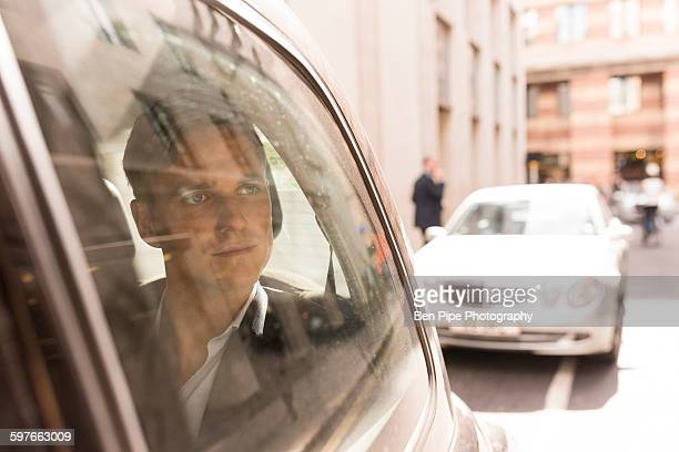 Businessman looking out of black cab, London, UK