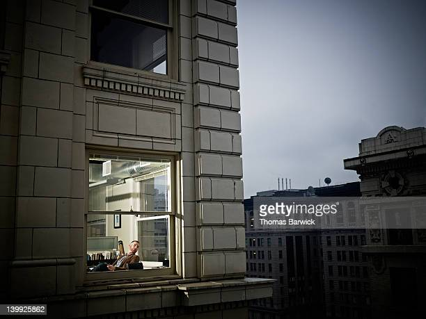 businessman looking out of corner office window - looking at view - fotografias e filmes do acervo