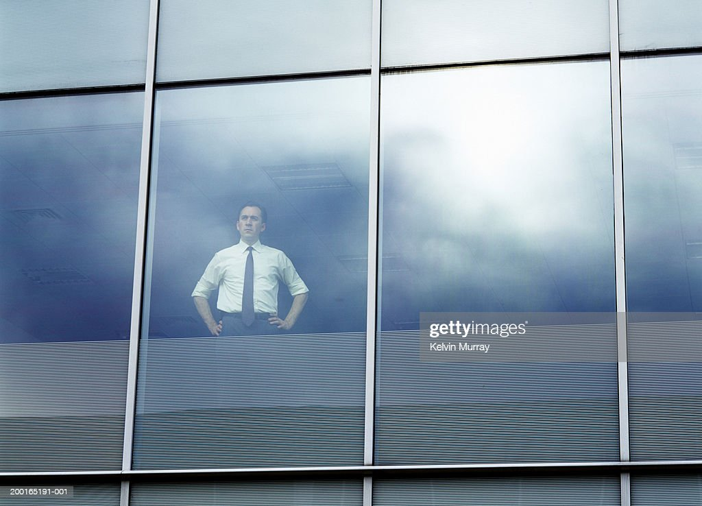 Businessman looking out of office window, low angle view : Stock Photo