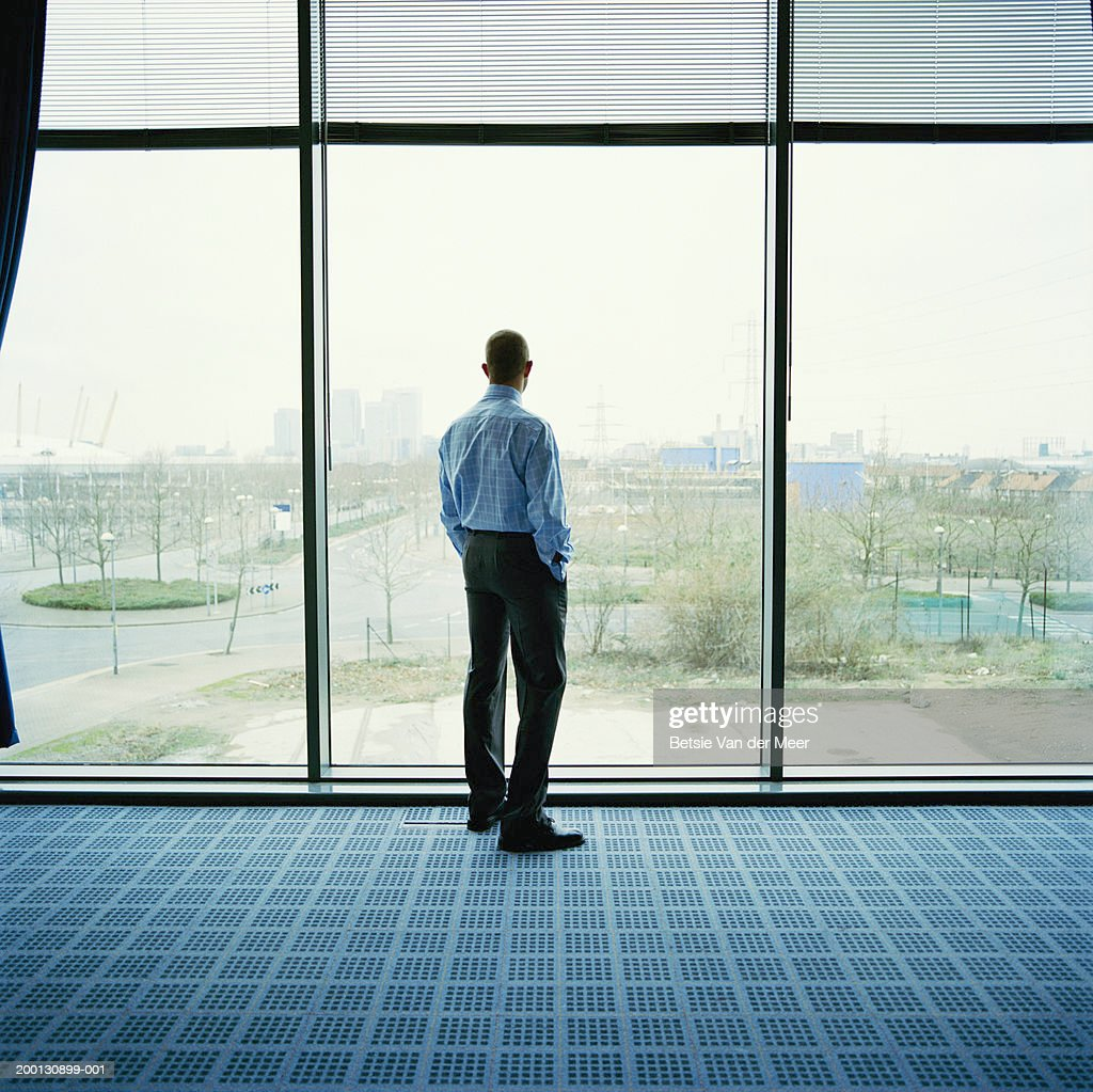 Businessman looking out of office window, rear view : Foto de stock