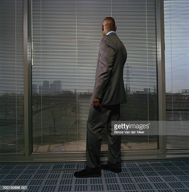 Businessman looking out of office window through blinds, rear view