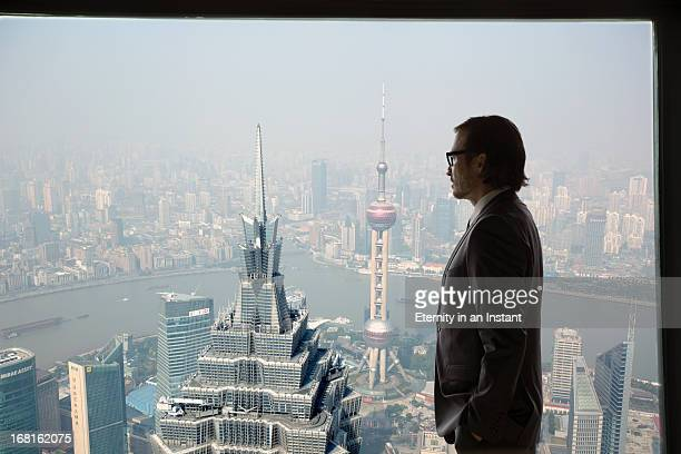 Businessman looking out of window at Shanghai Bund