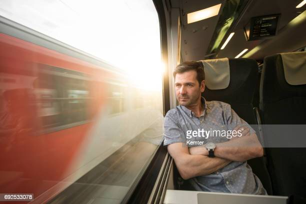 Homme d'affaires, regarde par la fenêtre pendant le déplacement en train