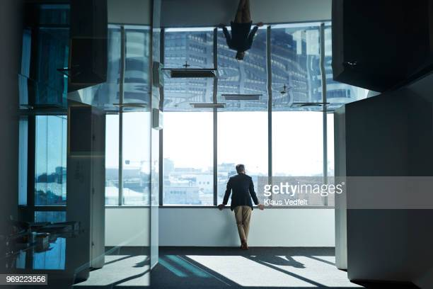 Businessman looking out of window from inside of big office building