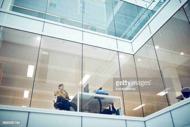 Businessman looking out of window in modern office