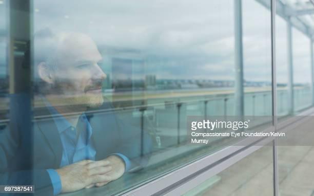 businessman looking out of window in office - edificios especiales fotografías e imágenes de stock