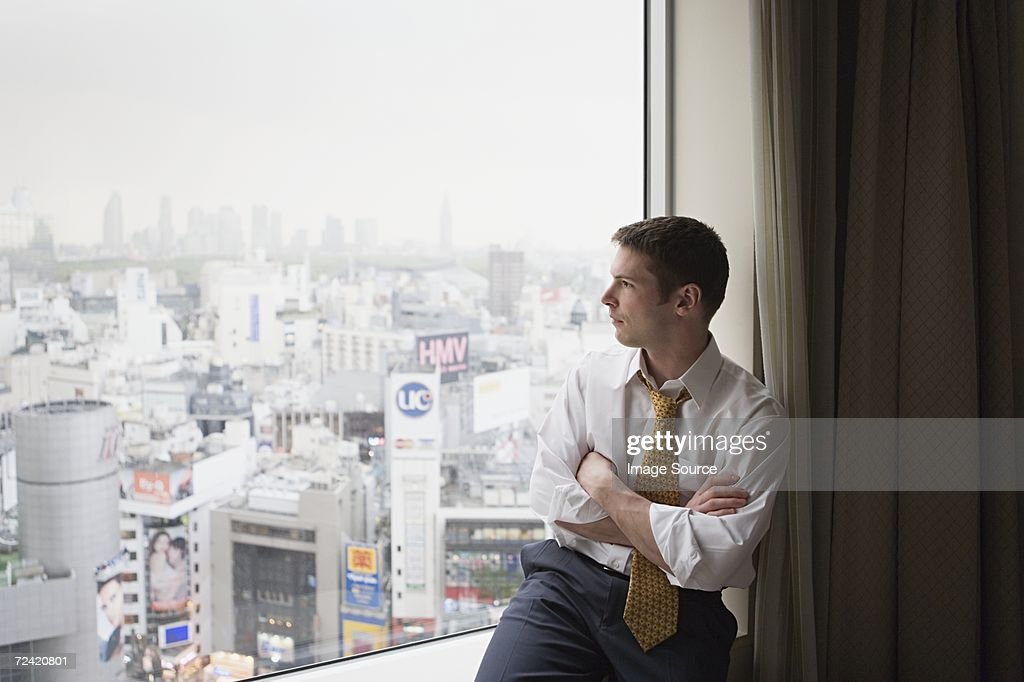 Businessman looking out of window : Stock Photo