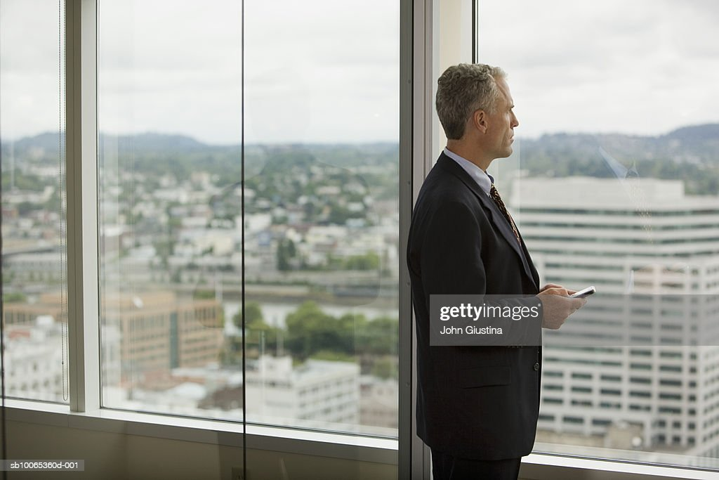 Businessman looking out of window, sid view : Foto stock