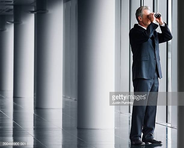 Businessman looking out of window with binoculars