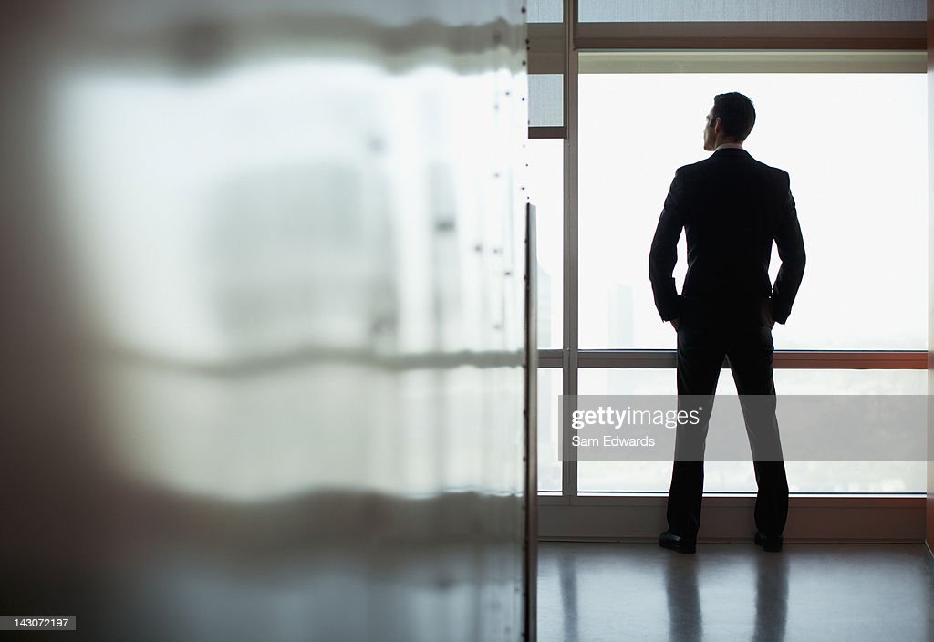 Businessman looking out office window : Stock Photo