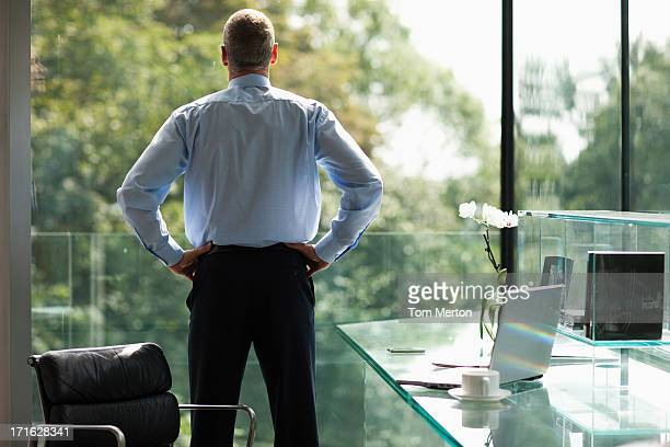 businessman looking out office window - hand on hip stock pictures, royalty-free photos & images