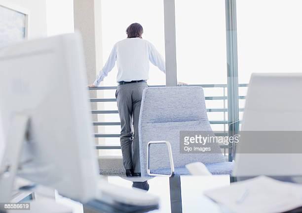 businessman looking out office window - ongeduldig stockfoto's en -beelden