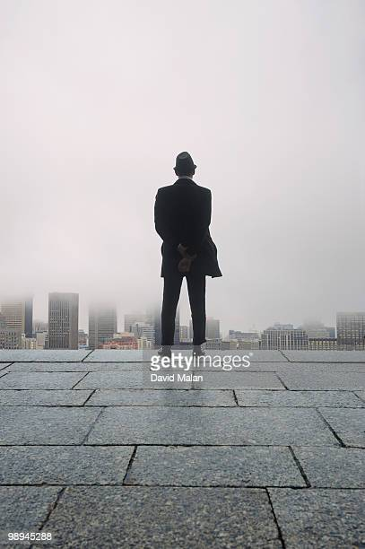 businessman looking out over city