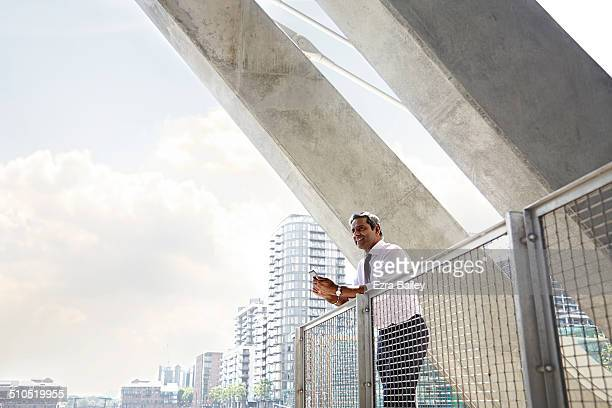 A businessman looking out over the city with phone