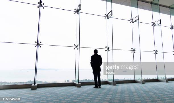 businessman looking out over the high rise window - overcoat stock pictures, royalty-free photos & images