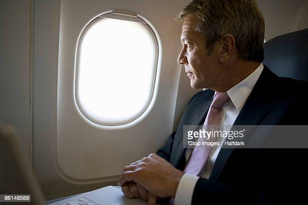 A businessman looking out the window of a plane