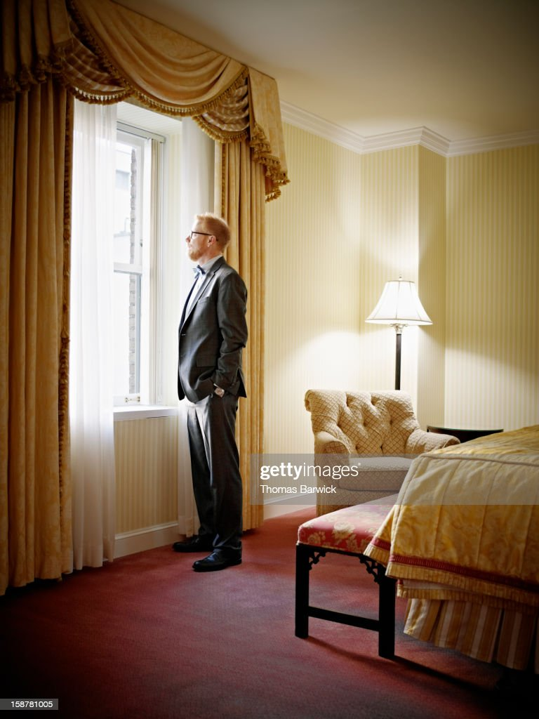 Businessman looking out window of hotel suite : Stock Photo