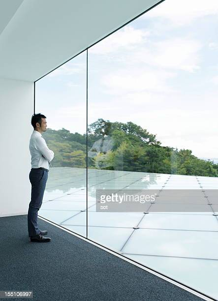 Businessman looking out windpw in office hallway