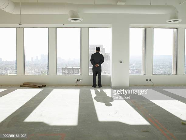 Businessman looking outside window in empty office space, rear view