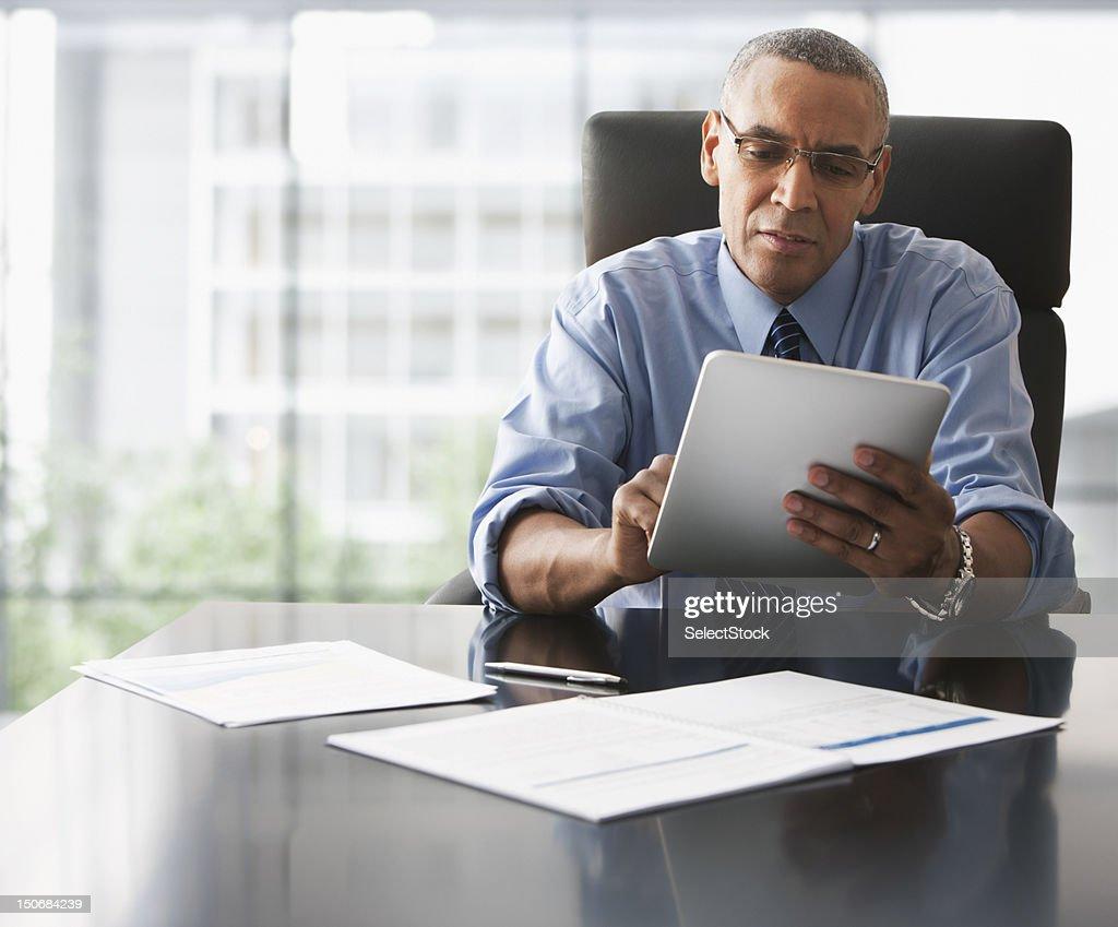 Businessman looking over electronic tablet : Bildbanksbilder