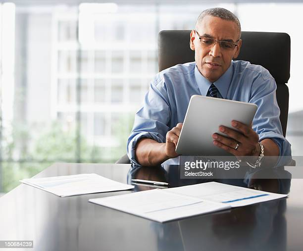 businessman looking over electronic tablet - ethnicity stock pictures, royalty-free photos & images