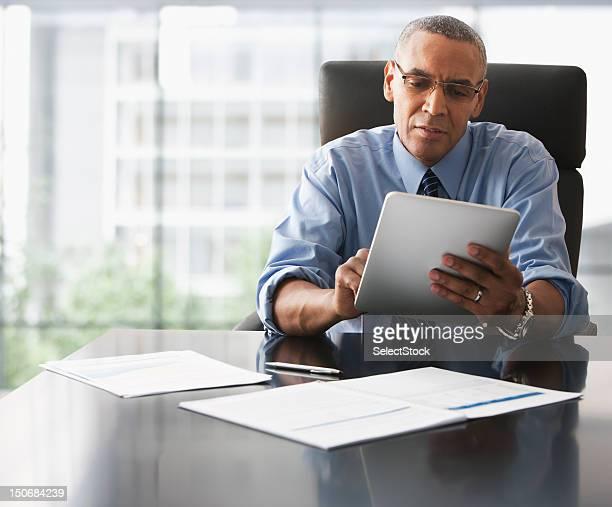 Homme d'affaires à la recherche sur la tablette électronique