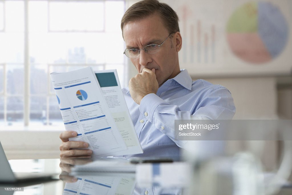 Businessman looking over report : Stock Photo