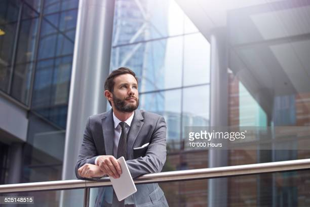 A businessman looking over the city and thinking.