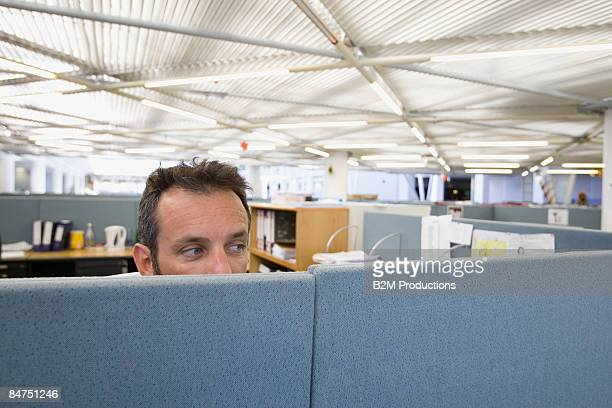 Businessman looking over wall in office