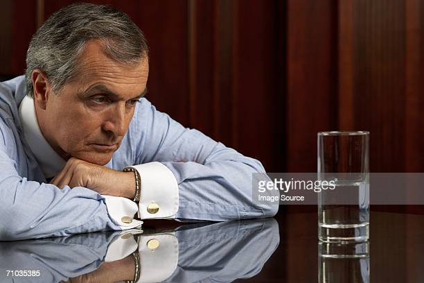 Businessman looking pessimistically at a glass of water
