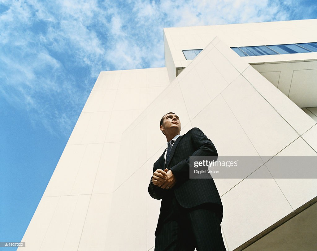 Businessman Looking Sideways Standing Outside a Modern Office Building : Stock Photo