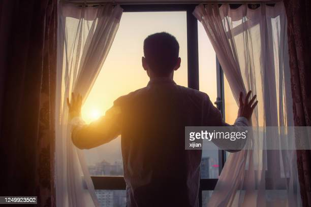 businessman looking sunrise standing by window - one man only stock pictures, royalty-free photos & images