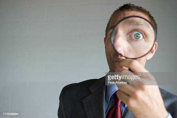 Businessman Looking Surprised with Magnifying Glass