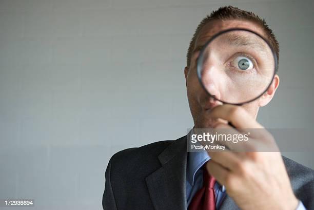 Überrascht Geschäftsmann mit Lupe