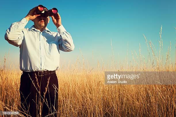 Homme d'affaires regardant à travers un jumelles