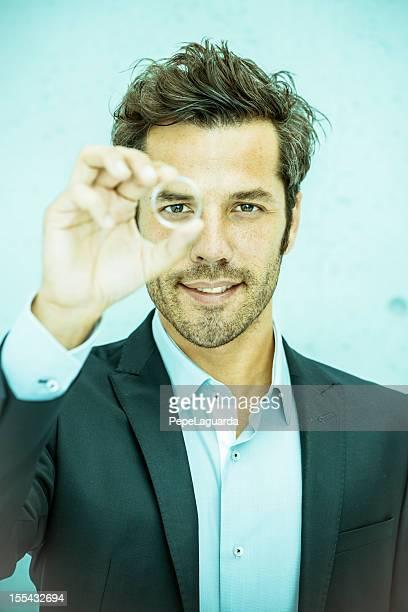 Businessman looking through a round lens