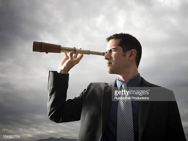 Hombre de negocios mirando a través de una catalejo