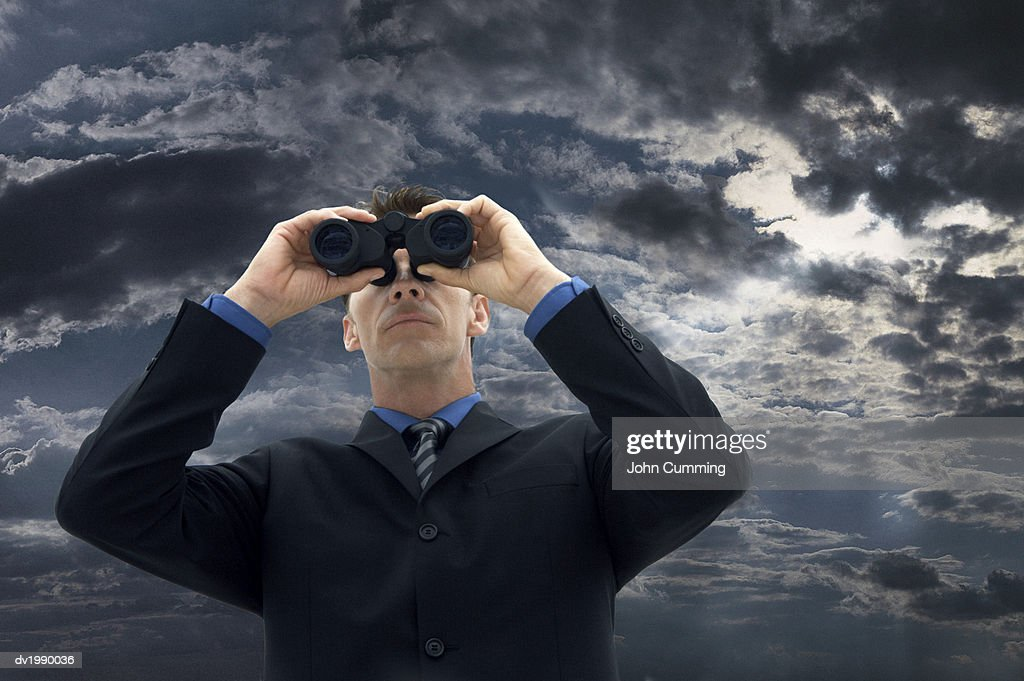 Businessman Looking Through Binoculars Against a Moody Sky : Stock Photo
