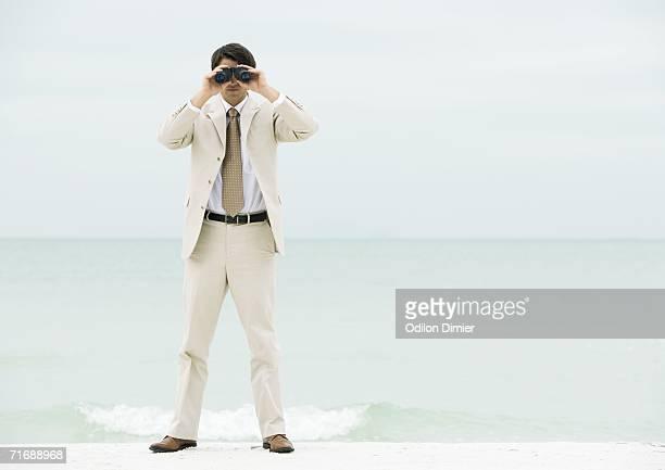 Businessman looking through binoculars, facing camera