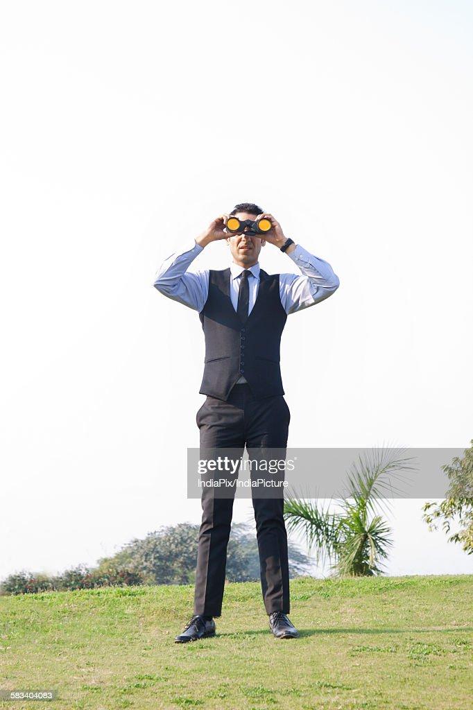 Businessman looking through binoculars , INDIA , DELHI : Stock Photo