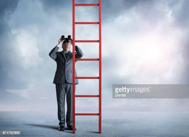 Homme d'affaires à la recherche par le biais de jumelles lève les yeux à grande échelle