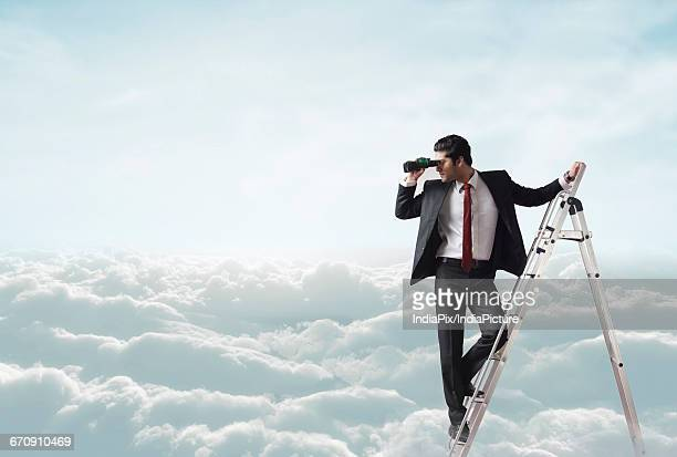 Businessman looking through binoculars on ladder