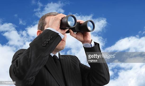 A businessman looking through binoculars