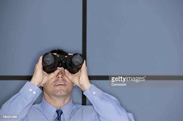 businessman looking through binoculars - homens de idade mediana imagens e fotografias de stock