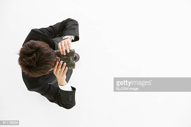 Businessman looking through binoculars, view from above, studio shot