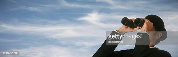 Businessman looking through binoculars XXL